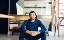 Уверенно и успешный бизнесмен сидя в большой студии работы Стоковое Изображение RF