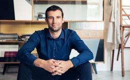 Уверенно и успешный бизнесмен сидя в большой студии работы Стоковая Фотография RF