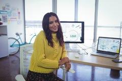 Уверенно коммерсантка сидя на столе офиса Стоковые Фото