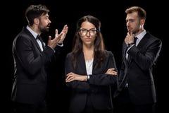 Уверенно коммерсантка смотря камеру пока ее коллеги обсуждая что-то позади Стоковые Фото
