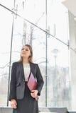 Уверенно коммерсантка смотря отсутствующий пока держащ папку на лобби офиса Стоковые Изображения