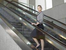 Уверенно коммерсантка стоя на эскалаторе Стоковое Фото