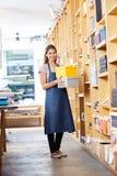 Уверенно коробки нося женского работника в магазине Стоковые Фото