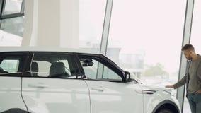 Уверенно красивый молодой человек смотрит красивый автомобиль в выставочном зале автомобиля и касается ему и идется вокруг автомо сток-видео
