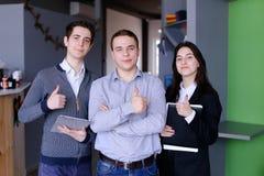 3 уверенно мальчики и студенты или работника девушек которые стоят w Стоковое Изображение