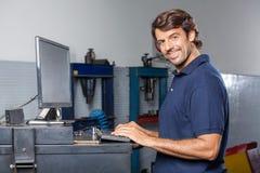 Уверенно механик используя компьютер в ремонтной мастерской Стоковое Изображение