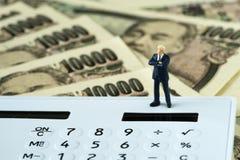 Уверенно миниатюрный финансовый бизнесмен стоя на калькуляторе Стоковое Фото