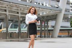 Уверенно молодая азиатская бизнес-леди при связыватель кольца стоя на внешнем офисе стоковое фото