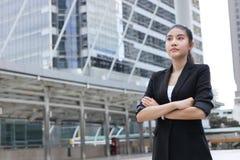 Уверенно молодая азиатская бизнес-леди смотря далеко на внешнем офисе Стоковая Фотография RF