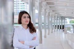 Уверенно молодая азиатская коммерсантка стоя, что и смотря препровождать на далеко на дорожке вне офиса Стоковые Фотографии RF
