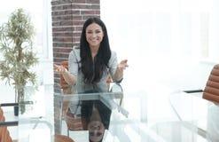 Уверенно молодая женщина - вождь сидя на таблице в конференц-зале Стоковые Изображения