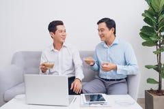 2 уверенно молодых предпринимателя используя компьтер-книжку обсуждают сообщают Стоковое Изображение RF