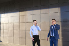 2 уверенно молодого человека, предприниматели, студенты говоря на phon Стоковое Изображение RF