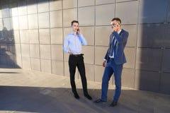 2 уверенно молодого человека, предприниматели, студенты говоря на phon Стоковые Изображения