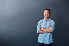 Уверенно молодой азиатский дизайнер стоя в современном офисе стоковое изображение