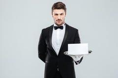 Уверенно молодой дворецкий держа пустую карточку на подносе стоковая фотография