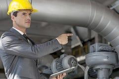 Уверенно молодой мужской менеджер с цифровой таблеткой указывая на машинное оборудование в индустрии Стоковые Изображения RF