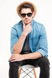 Уверенно молодой человек в шляпе и солнечных очках сидя на стуле Стоковые Изображения RF