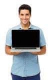 Уверенно молодой человек показывая компьтер-книжку стоковое фото rf