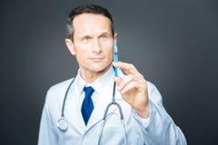 Уверенно мужской доктор фокусируя его внимание на шприце стоковая фотография rf