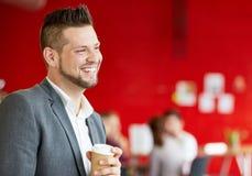 Уверенно мужской дизайнер имея кофе на работе в красных творческих размерах офиса Стоковая Фотография