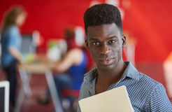 Уверенно мужской дизайнер работая и рассматривая документы внутри папки в красных творческих размерах офиса Стоковое фото RF