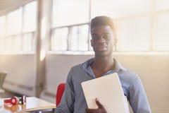 Уверенно мужской дизайнер работая и рассматривая документы в папке внутри красных творческих размеров офиса Стоковые Изображения RF