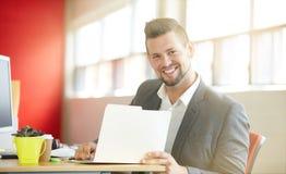 Уверенно мужской дизайнер работая и рассматривая документы на папке в красных творческих размерах офиса Стоковые Изображения