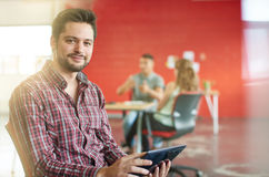 Уверенно мужской дизайнер работая на цифровой таблетке в красных творческих размерах офиса Стоковые Фото