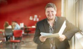 Уверенно мужской дизайнер рассматривая документы в папке на красных творческих размерах офиса Стоковое Изображение