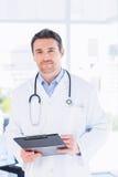 Уверенно мужской доктор с доской сзажимом для бумаги в больнице Стоковое Изображение RF