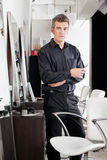 Уверенно мужской парикмахер с ножницами на салоне Стоковые Фотографии RF