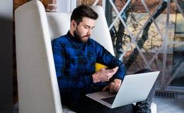 Уверенно мужской предприниматель проверяя сообщение на мобильном телефоне стоковая фотография