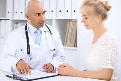 Уверенно облыселый человек доктора советует с его женским пациентом Стоковое Фото