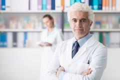 Уверенно доктор представляя в его офисе стоковая фотография