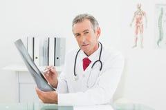 Уверенно доктор с изображением рентгеновского снимка легких в офисе Стоковая Фотография RF