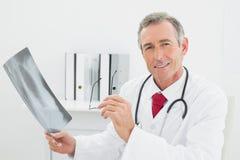 Уверенно доктор с изображением рентгеновского снимка легких в офисе Стоковое фото RF