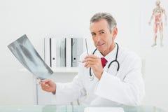 Уверенно доктор с изображением рентгеновского снимка легких в офисе Стоковые Фото