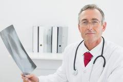 Уверенно доктор с изображением рентгеновского снимка легких в офисе Стоковые Изображения