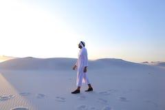 Уверенно парень, араб идет в середину белой пустыни и наслаждается l Стоковые Изображения RF