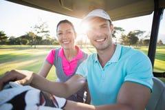 Уверенно пары игрока в гольф сидя в гольфе bugggy Стоковое Фото