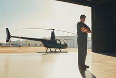 Уверенно пилотное положение в ангаре самолета стоковое фото rf