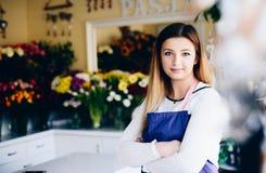 Уверенно предприниматель молодой женщины магазина флориста с пересеченными оружиями стоковое изображение