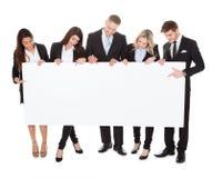 Уверенно предприниматели держа пустое знамя Стоковое фото RF