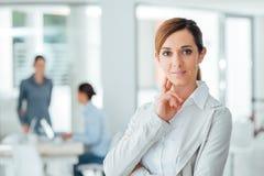 Уверенно предприниматель женщины представляя в ее офисе Стоковое Изображение RF