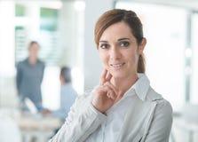 Уверенно предприниматель женщины представляя в ее офисе Стоковые Изображения RF