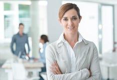 Уверенно предприниматель женщины представляя в ее офисе Стоковые Фото
