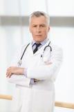 Уверенно профессионал здравоохранения. Уверенно зрелая стойка доктора стоковое изображение rf