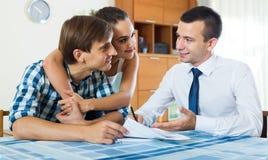 Уверенно продавец и молодые супруги обсуждая контракт Стоковые Фотографии RF