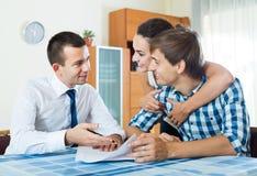 Уверенно продавец и молодые супруги обсуждая контракт Стоковое фото RF